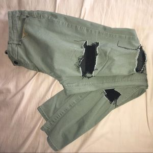 Skinny fitted distressed dark green pants.